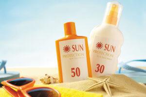 Sun Cream in the Sand with Sunglasses on a Beach